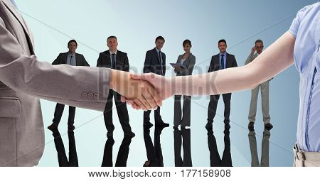 Digital composite of Handshake in front of business people with blue background