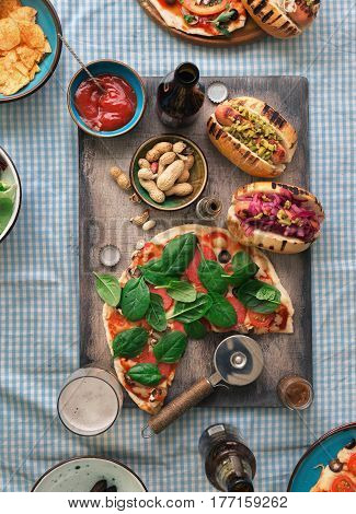 Dinner table concept. Homemade pizza different hot dogs beer and snack for beer on rustic table top view