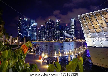 Singapore, Singapore - February 11, 2017: People move alongside the Marina Bay Sands in the Waterfront by night in Singapore.