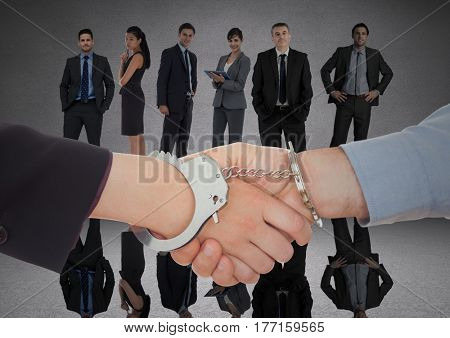 Digital composite of Handshake with handcuffs in front of business people in grey room