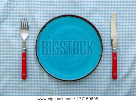 Empty blue ceramic plate with knife and fork close up top view
