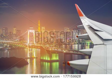 Airplane wing over Tokyo tower and rainbow bridge in Tokyo Japan.