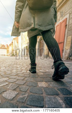 Low angle view of female tourist with backpack walking down the street paved with cobblestone in old european city