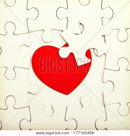 Jigsaw puzzle with blank white pieces and red heart.