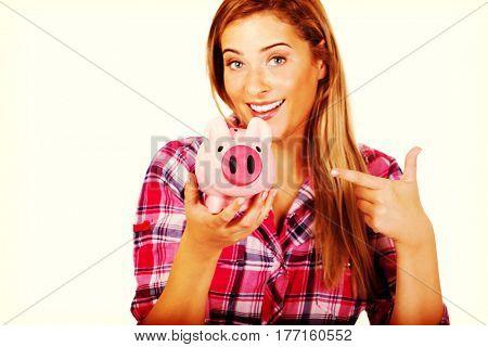 Smiling young woman holding piggybank