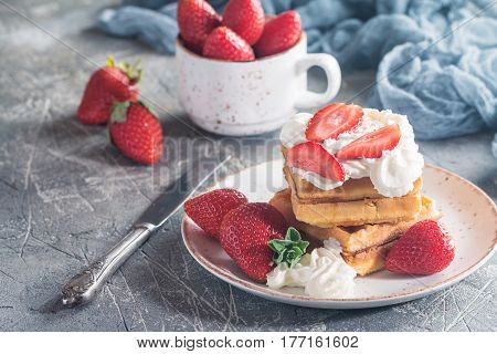 Waffle dessert with cream sauce and strawberry on gray rustic background