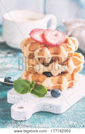 Stack of Homemade Belgian waffles with strawberries, blueberries and syrup on blue table