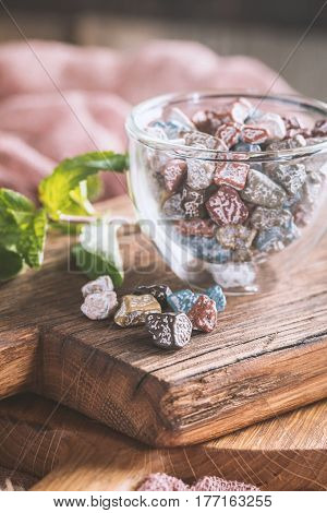 Multicolor bonbon sweets stone candies in glass bowl on wooden background