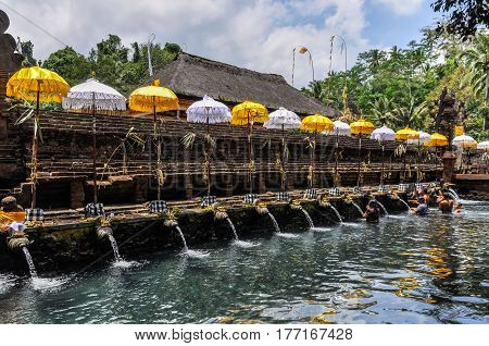 BALI, INDONESIA - SEPTEMBER 27, 2012: People taking purifying bath in the Tirta Empul Temple in Bali Indonesia