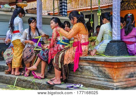 BALI, INDONESIA - SEPTEMBER 27, 2012: Balinese people prepare the offerings for the full moon ritual in the Tirta Empul Temple in Bali Indonesia
