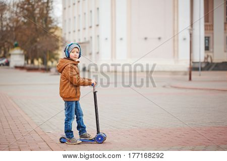 Cute little boy riding on scooter. Children actitvities outdoor in early spring