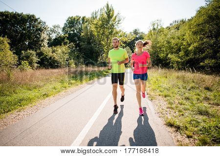 Friends jogging together in  park on summer sunny day