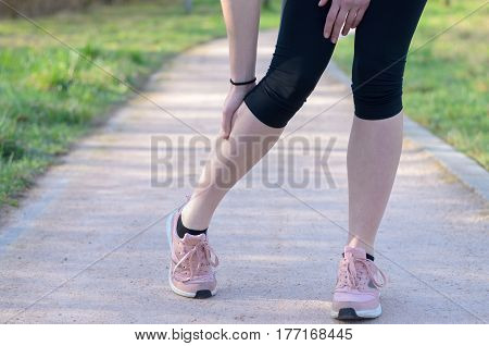 Young Woman Jogger Suffering From Calf Cramps