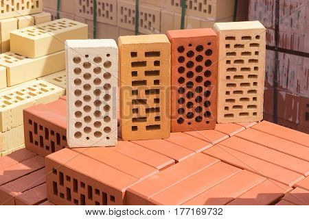 Four perforated bricks of white yellow and red colors with round and rectangular holes on a pallet with bricks on the background other bricks on a warehouse