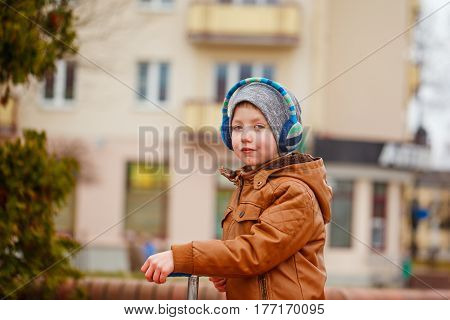 Cute little boy riding on scooter. Children actitvities outdoor in early spring.