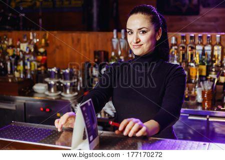 A barman girl at a bar ready to take an order. Horizontal photo