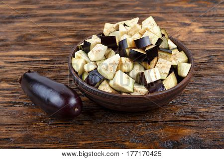 Diced eggplants in a clay plate on a wooden background next to it is a whole eggplant. Horizontal photo