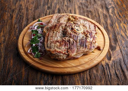 Medium rare grilled Beef steak Ribeye with onion on cutting board on dark wooden background.