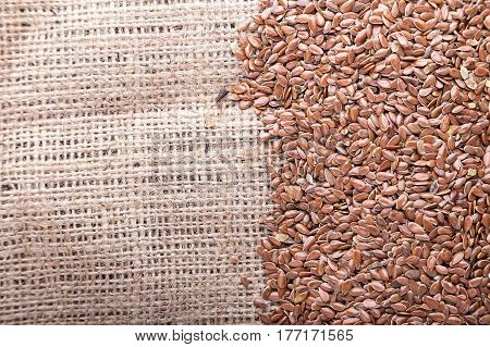 Flax seeds are scattered on a napkin of burlap lies next to wooden spoon with flax seeds