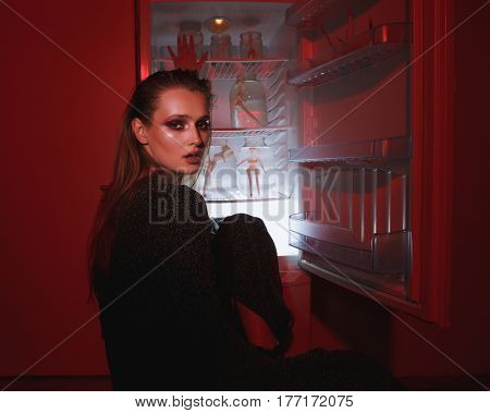 Back view of woman in dress which sitting near the fridge and looking at camera. Conceptual photo