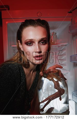Close up picture of woman in dress which holding jar with doll and looking at camera while sitting near the fridge. Vertical image. Conceptual photo