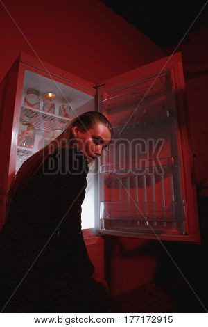 Side view of mystery woman in dress which standing near the fridge and looking away. Conceptual picture. Vertical image