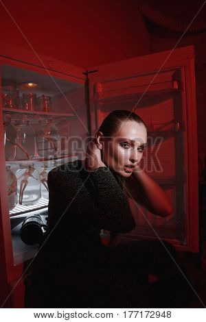 Side view of mystery woman in dress which sitting near the fridge and combing her hair while looking at camera. Vertical image. Conceptual picture
