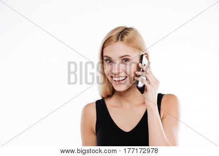 Photo of cheerful fitness lady standing and posing isolated over white background. Looking at camera and talking by mobile phone.