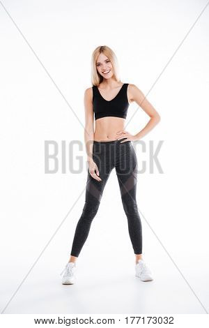 Picture of happy beautiful fitness woman standing and posing isolated over white background. Looking at camera.