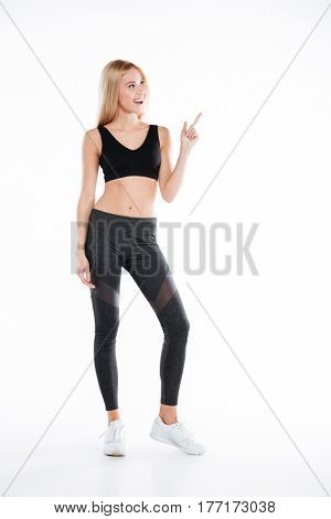Photo of smiling pretty fitness woman standing and posing isolated over white background. Looking aside and pointing to copyspace.