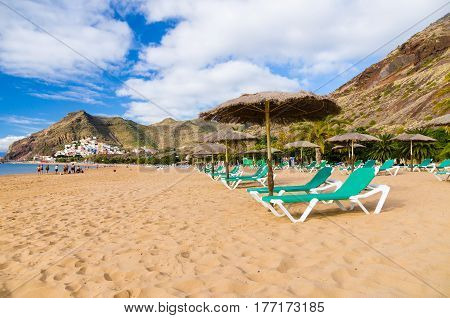 Palapa and chaise-longue on golden sand of Playa de las Teresitas. San Andres village on background Tenerife Spain