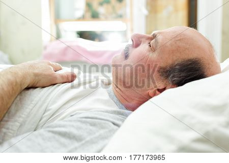 An elderly man lies on a bed and is dozing. Rest after work day in bed.