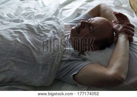 The elderly man is fast asleep covered by a white blanket. Healthy sleep at night