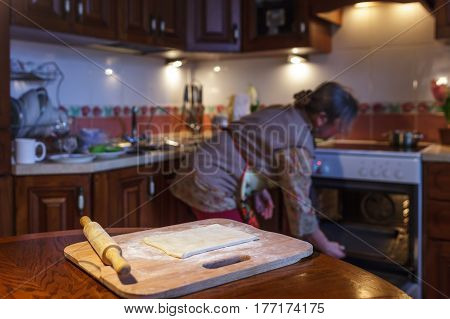 A woman prepares pies warms up the oven. Cooking homemade cakes
