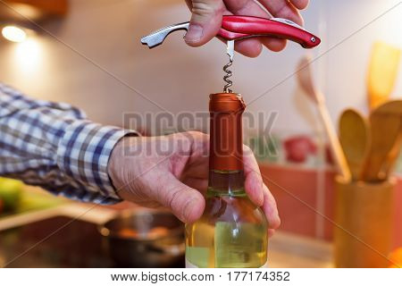 A man opens a bottle of white wine with a corkscrew