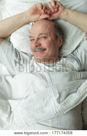 An elderly man slyly lies on the bed smiling. Top-down view