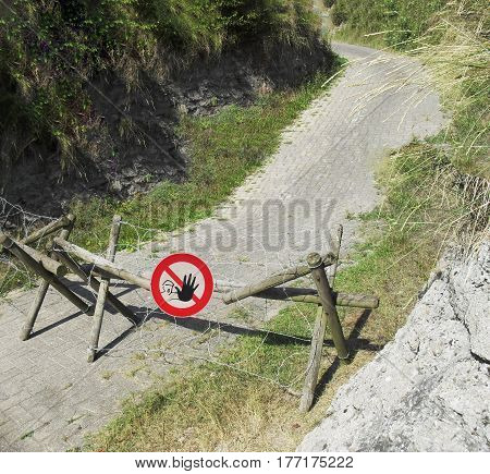 Old wooden barricade with rusty barbed wire border fence.