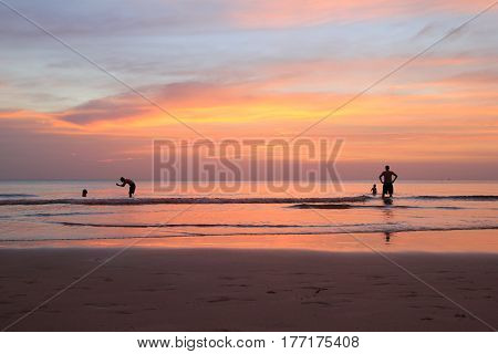Travel to island Koh Chang, Thailand. The walking people on the beach on the colorful sunset.