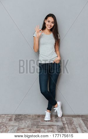 Vertical image of smiling woman showing ok sign and looking at camera while holding arm in pocket and posing in studio over gray background