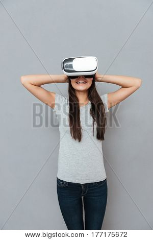 Vertical image of happy woman using virtual reality device and holding her head over gray background