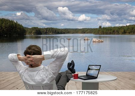 Young businessman relaxes on a pier of Lake