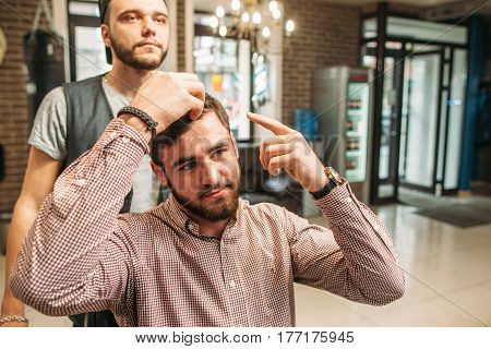 Confident man tell about haircut he want. Businessman show stylist how to cut his hair, free space. Barber shop, beauty, fashion, modern lifestyle concept