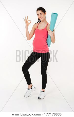 Full length portrait of pregnant fitness woman showing ok sign and looking at camera while holding fitness man over white background