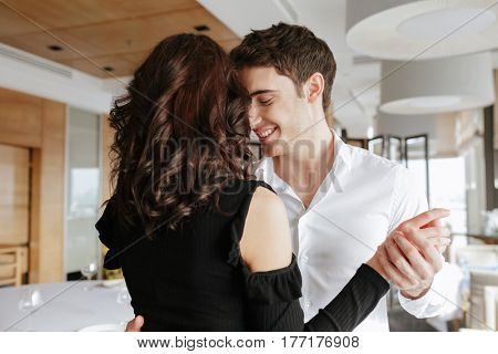 Photo of young loving happy couple dancing in restaurant indoors. Looking aside.