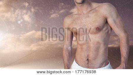 Digital composite of Fitness man Torso against raining and cloud sky