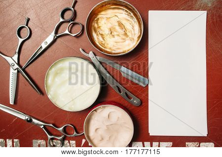 Tools for hairstyling with blank card flat lay. Top view on red table with scissors, razor, hair wax and empty white paper, free space for text