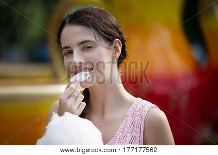 Cute Caucasian Girl In Amusement Park Is Eating Pink Candyfloss. Portrait Of Happy Attractive Young