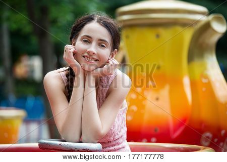 Attractive Happy Smiling Girl In An Amusement Park Sitting On Carousel.