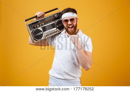 Picture of happy young man wearing sunglasses holding tape recorder dressed in white t-shirt isolated over yellow background. Looking at camera make winner gesture.