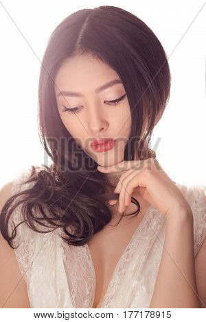 Beautiful young asian woman with long curly hair on white background. Close-up portrait of gorgeous girl in white lacy wedding dress looking away